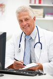 Senior doctor at desk taking notes Royalty Free Stock Image