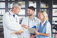 Senior doctor discussing with coworkers while standing Stock Photos