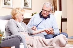 Senior doctor and elderly patient stock photography