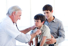 Senior doctor examining a boy with his father Royalty Free Stock Photography