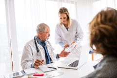 Senior doctor examining a senior woman in office. Senior doctor examining a senior woman. A nurse holding IV infusion royalty free stock photography