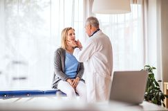 Senior doctor examining a young woman in office. Senior doctor examining a young woman. A doctor and a patient at the doctors office stock image