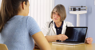 Senior doctor explaining neck x-ray to Mexican woman patient Royalty Free Stock Photo