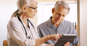 Senior doctor expressing health concerns with elderly man patient Royalty Free Stock Photography