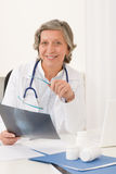 Senior doctor female sit behind office desk Stock Image