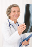 Senior doctor female smiling hold x-ray Stock Photos
