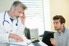 Senior doctor hesitating to tell truth to patient. Senior doctor hesitating to tell the truth to his patient Stock Image