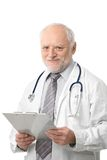 Senior doctor holding papers smiling Stock Images