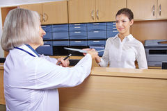 Senior doctor at hospital reception. Getting medical records stock images