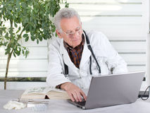 Senior doctor with laptop Royalty Free Stock Image