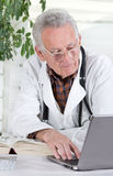 Senior doctor with laptop Stock Photography