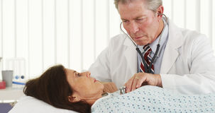 Senior doctor listening to mature patient's heart Royalty Free Stock Images