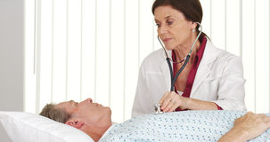 Senior doctor listening to mature patient's heart. In hospital bed Stock Image