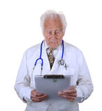 Senior doctor looking at clip board Stock Photo