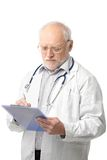Senior doctor looking at clipboard Royalty Free Stock Images