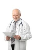 Senior doctor looking at papers smiling. Portrait of senior doctor looking at papers, smiling, isolated on white Stock Photo