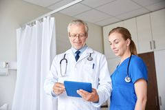 Senior doctor and nurse with tablet pc at hospital Stock Photography