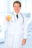 Senior Doctor Offering Medicine Stock Photography