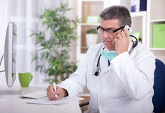Senior doctor in the office talking on a mobile phone and writes Stock Photos