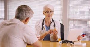 Senior doctor prescribing medication to elderly patient Stock Photos