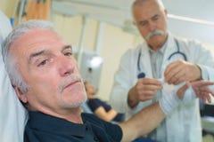 Senior doctor putting bandage on elder mans arm royalty free stock photo