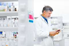 Senior doctor/scientist using his tablet computer at work Stock Photo