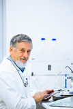 Senior doctor/scientist using his tablet computer at work Royalty Free Stock Photos