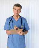 Senior doctor in scrubs facing camera. Senior male caucasian doctor with stethoscope in medical scrubs and confidently facing the camera in portrait Stock Photos