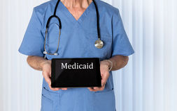 Senior doctor in scrubs facing camera. Senior male caucasian doctor with stethoscope in medical scrubs looking up and holding electronic tablet for Medicaid Stock Photo