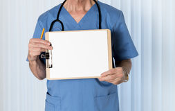 Senior doctor in scrubs with message. Senior male caucasian doctor with stethoscope in medical scrubs and holding clipboard for message Stock Photo