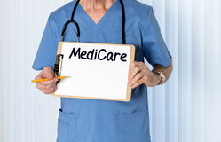 Senior doctor in scrubs with message. Senior male caucasian doctor with stethoscope in medical scrubs and holding clipboard for Medicare message with pencil for Royalty Free Stock Image