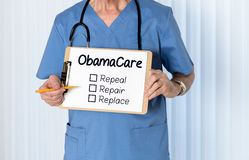 Senior doctor in scrubs with message. Senior male caucasian doctor with stethoscope in medical scrubs and holding clipboard for Obamacare message with pencil for Royalty Free Stock Photo