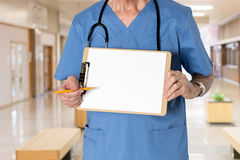 Senior doctor in scrubs with message. Senior male caucasian doctor with stethoscope in medical scrubs and holding clipboard for message with pencil for emphasis Royalty Free Stock Images