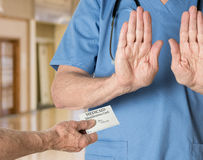 Senior doctor in scrubs refusing Medicaid Card. Senior caucasian doctor in scrubs in hospital refusing to treat a patient with a Medicaid card Royalty Free Stock Images