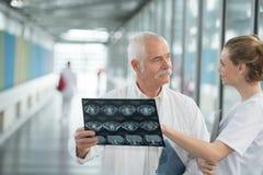 Senior doctor showing nurse patients xray in hospital corridor. Senior Royalty Free Stock Photo