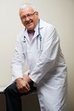 Senior Doctor Sitting On Desk Stock Photography