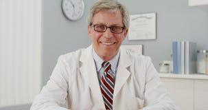 Senior doctor sitting at desk smiling at camera Stock Photography