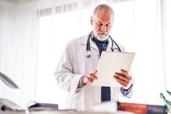 Senior doctor with tablet in his office. stock photography