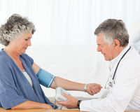 A senior doctor taking the blood pressure Stock Photos