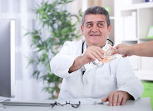 Senior doctor taking bribes from patients Stock Image