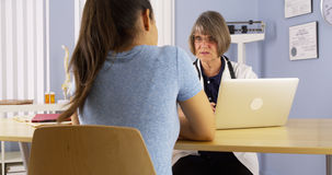 Senior doctor taking notes on laptop and talking to patient Royalty Free Stock Photos
