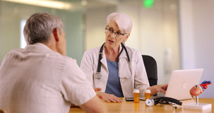 Senior doctor talking with elderly man in the office Royalty Free Stock Photos
