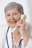 Senior doctor talking on phone Stock Images