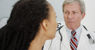 Senior doctor talking to adult woman in the office Stock Photos