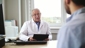 Senior doctor talking to male patient at hospital. Medicine, healthcare and people concept - senior doctor with tablet pc computer talking to young male patient stock video