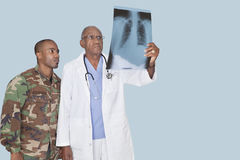 Senior doctor with US Marine Corps soldier looking at x-ray report over light blue background Stock Image