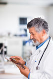 Senior doctor using his tablet computer Stock Photos
