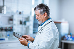 Senior doctor using his tablet computer at work Stock Photo