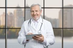 Senior doctor using his tablet computer at work. royalty free stock image