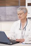 Senior doctor using laptop. Computer sitting in office Stock Photos